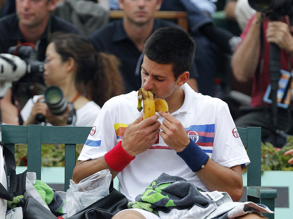 Novak Djokovic grabs a snack during a match.