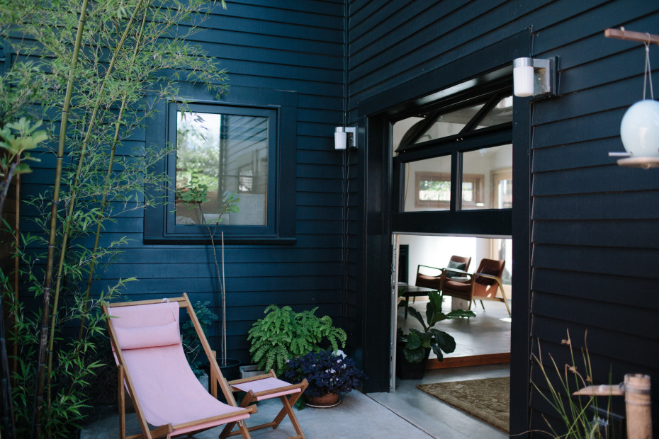 To contrast the dark exterior, the interiors are painted white. Cedar siding painted in Jet Black by Benjamin Moore contrasts the natural wood fencing.