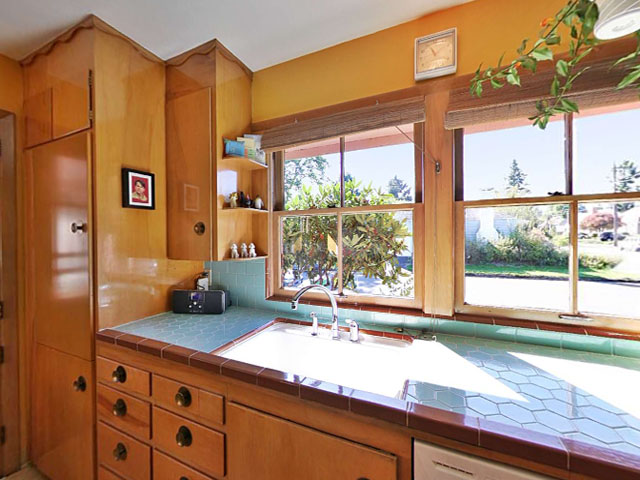The kitchen was restored to its 1954 glamour with the original birch plywood cabinets, vintage hardware, and ceramic tile countertops. Modern upgrades were worked into the design with subtlety—the new built-in Leibherr counter depth refrigerator (left) was faced with the same plywood as the rest of the cabinetry.