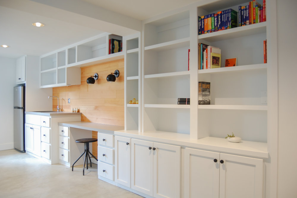 By removing a false wall that oddly separated the space and blocked light, a custom wall-to-wall built-in was incorporated along the rear length of the basement. The integrated kitchenette was important for easy access to kids' snacks and clean-up after craft projects. A lowered desk space is utilized for study, gift-wrapping, and card-making. Reclaimed fir plank on the walls and lights from Schoolhouse Electric tie into the same finishes found in the upper level of the home.