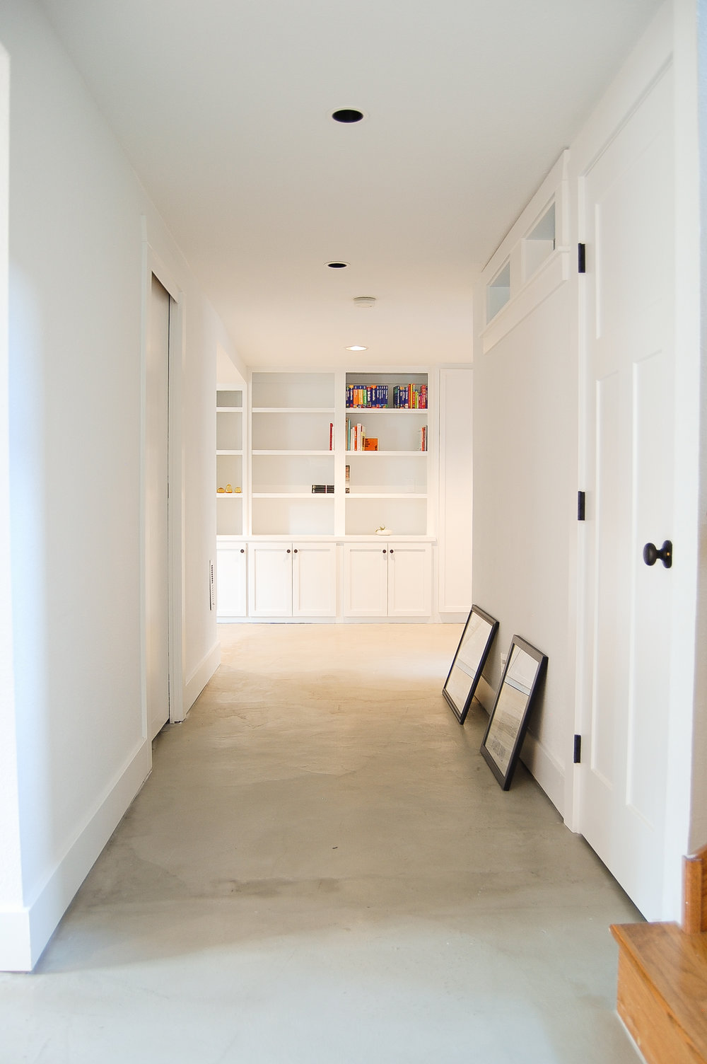 Ample shelves offer plenty of space for these avid book collectors to organize using the dewey decimal system, while leaving space to showcase collected objects and art. An extra-wide hallway keeps the basement spacious and open, with expansive walls to display a growing art collection.