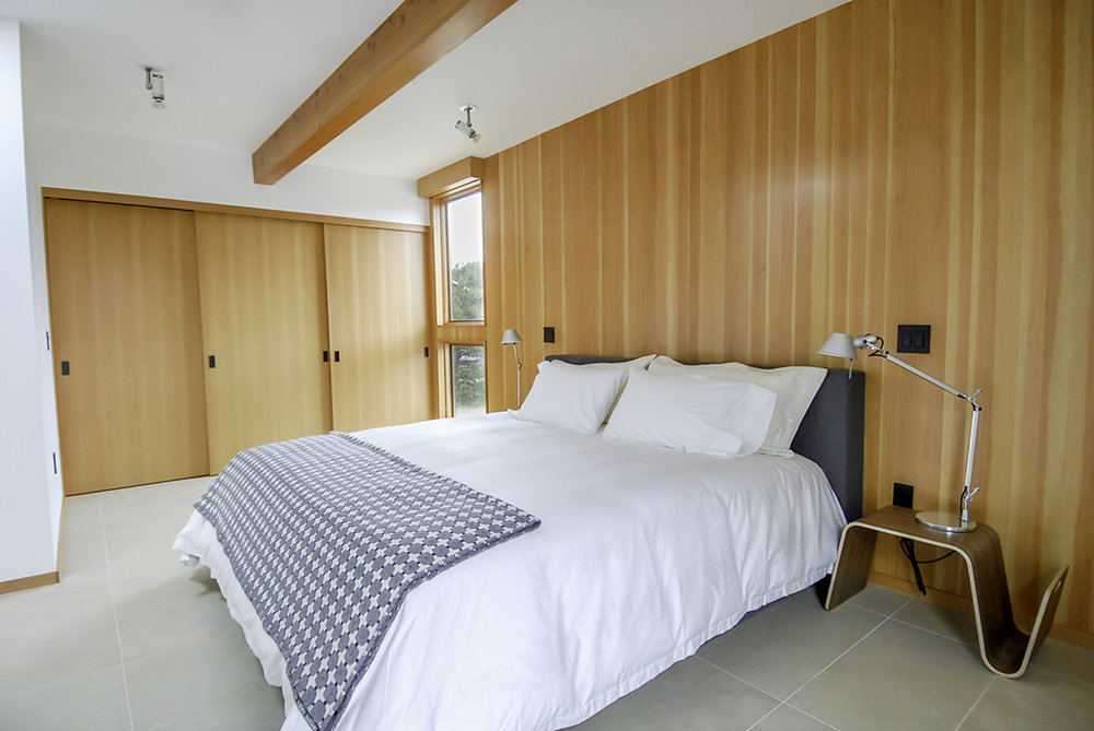 Fir tongue-and-groove wood was applied to all three of the bedrooms on one wall for warmth and depth. This photo of the master bedroom illustrates the beam running through the home, and the detail of the wood valance for the window shades.