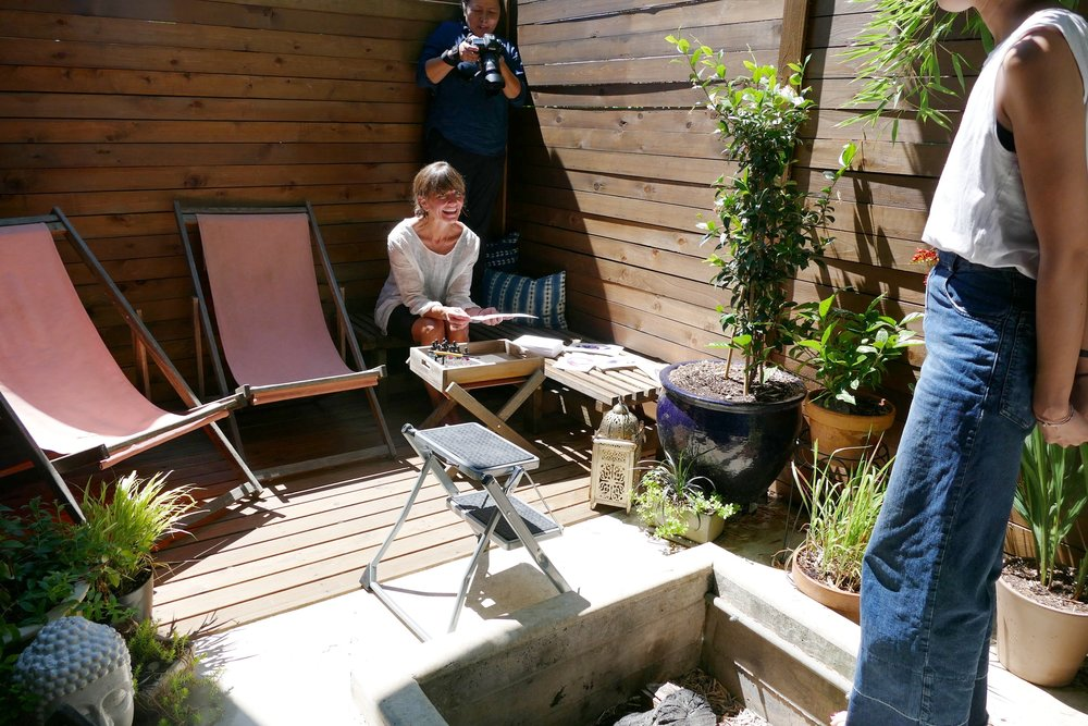 As part of the lifestyle images, they wanted to capture how Shannon used her patio. Other than reading and eating, her water color paintings seemed to be the preferred hobby to highlight. The step stool is the photographer's tool for hovering above and getting that perfect angle. In this take, she wanted a POV, so tucked in behind Shannon while she worked. Nana is in the foreground directing Shannon on how much happiness to exude on a scale of 1-10. This is happiness level 5 and outfit #2.