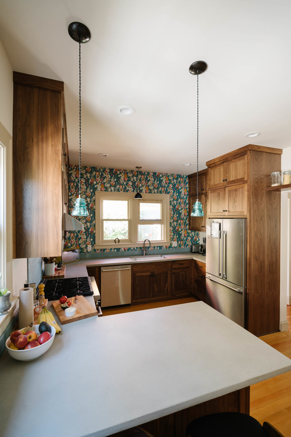 Inset cabinetry is in keeping with the style of the home, while solid walnut doors and natural concrete counters keep it feeling modern.