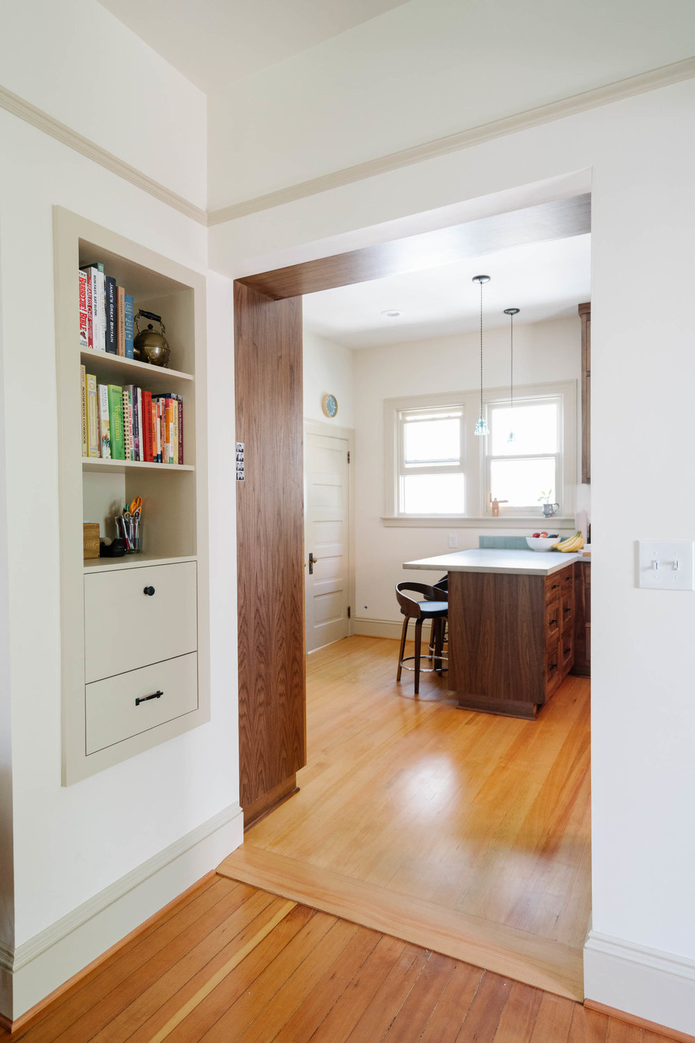 A wide opening from the kitchen into the dining room provides good connectivity. Cabinets and an overhead display shelf flank the passage. Built-ins in unique locations optimize storage.