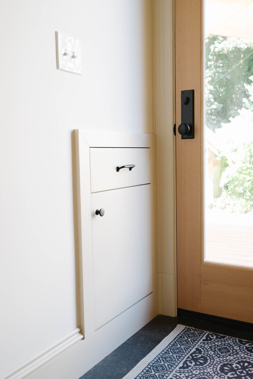 A new built-in cabinet for shoe storage and drawer for gloves is conveniently located in the mudporch. This feature recesses into the kitchen cabinet run, utilizing the typically wasted space in a lower corner cabinet.