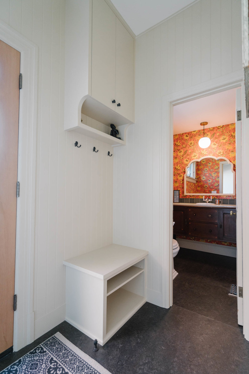 A sweet powder room off the mudporch was wrapped with a wallpaper featuring some of the same tones as the wallpaper in the kitchen, creating a cohesive feel through the entire remodel. This vibrant little space is now a destination with big presence.
