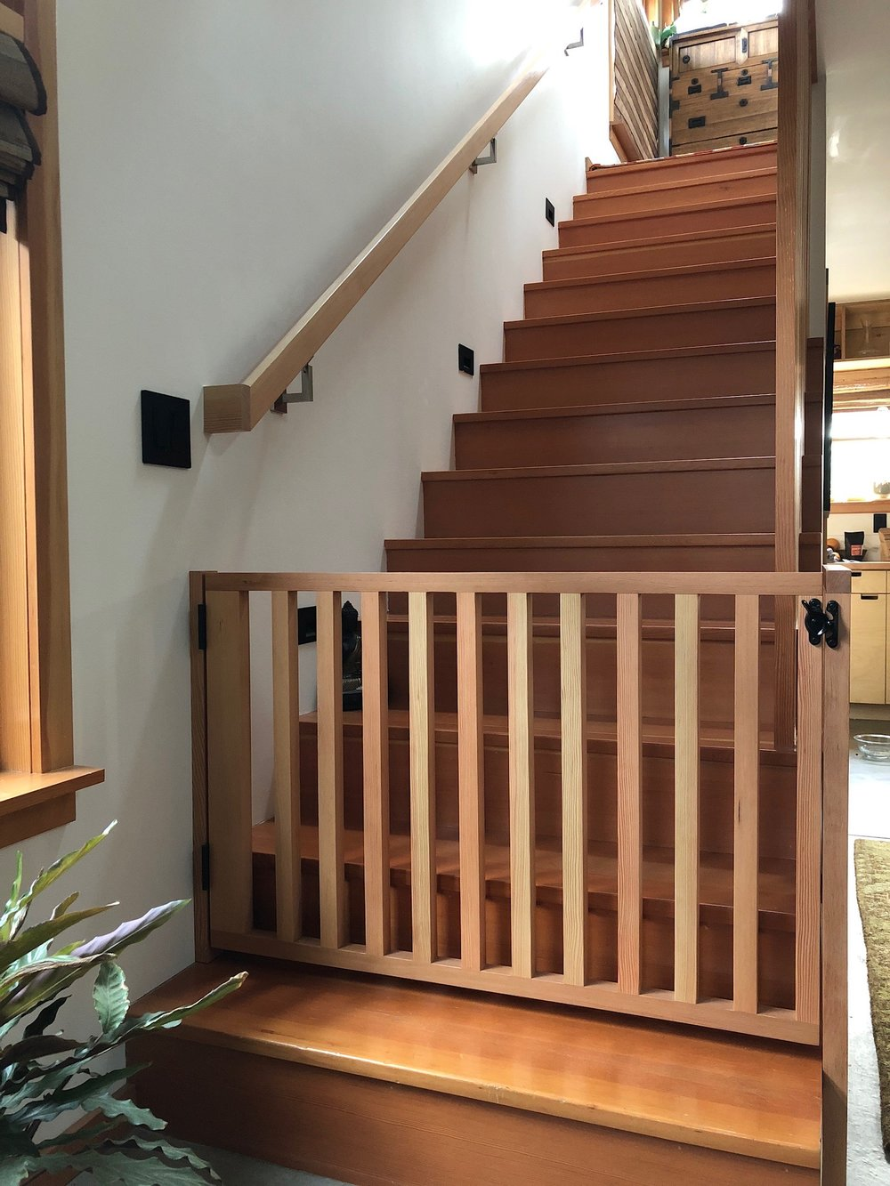 The gate is made of fir to match the existing trim throughout the home. It was installed without having to drill into the wood -- just a few fasteners into the drywall that can easily be patched over when the gate is no longer necessary.
