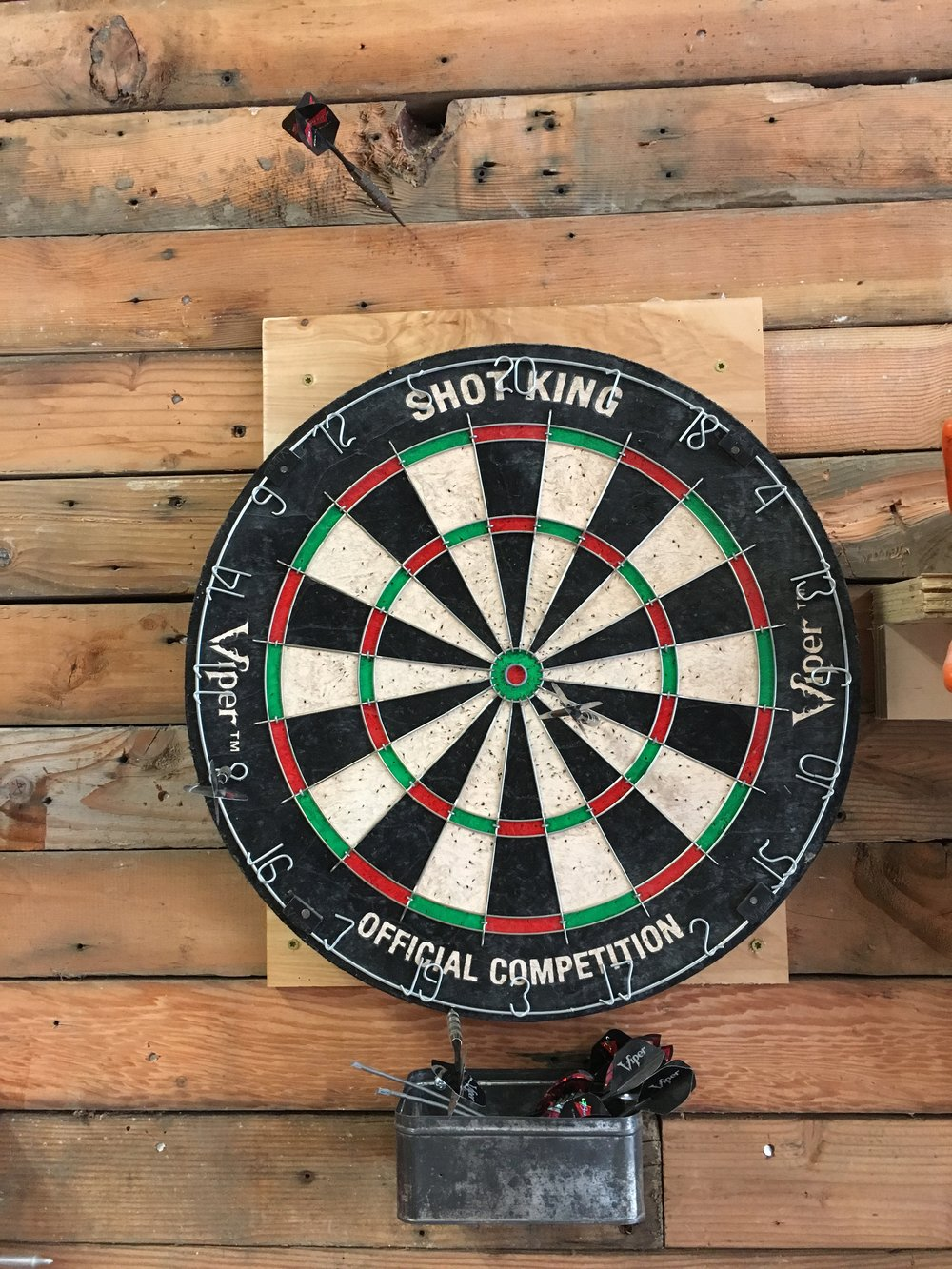 Custom wall built of leftover wood in Cody's studio, and a vintage dartboard for taking a moment to mull design ideas and blow off a little steam.