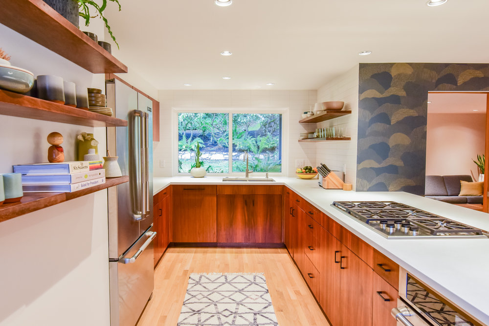 We recommended trying to save the existing cabinetry for this u-shaped kitchen remodel, and the results are stunning. Cement Elegance white concrete countertops provide a modern feel. A former wall of cabinets was opened to the dining room, allowing for unobstructed views of the forest beyond.