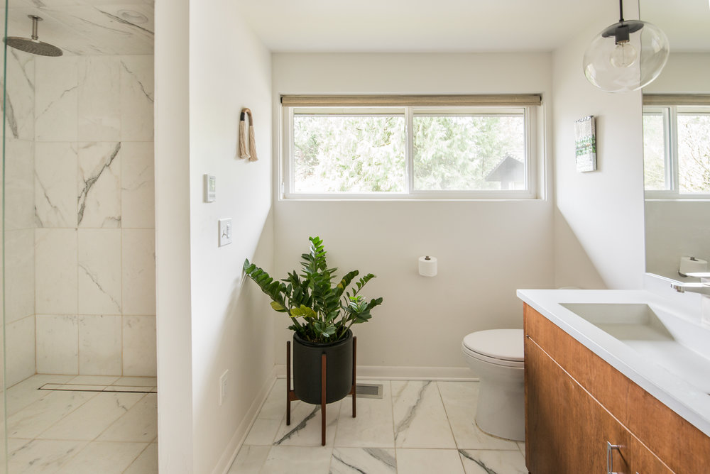 Master bath update with restored cabinetry. Calcutta marble on floors and shower walls is always a perfect choice, especially when paired with the Cement Elegance white countertops.