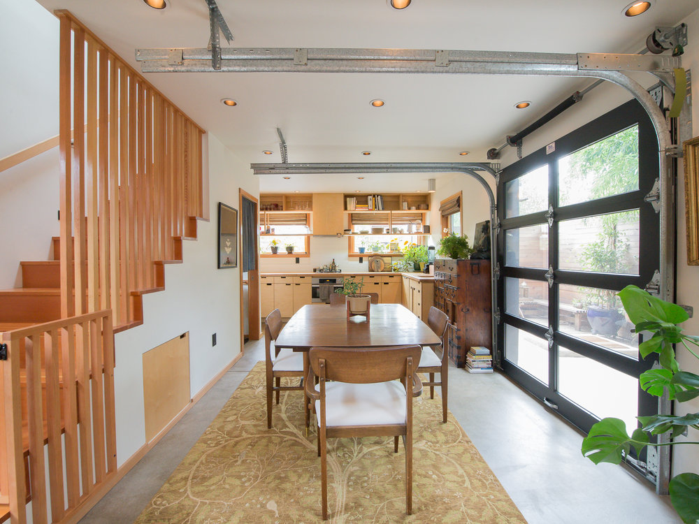In the dining area, a garage door opens up to the adjacent courtyard, thereby doubling the size of the space. The garage door simply lifts out of the way and does not need the same amount of space as french doors or even accordion walls.