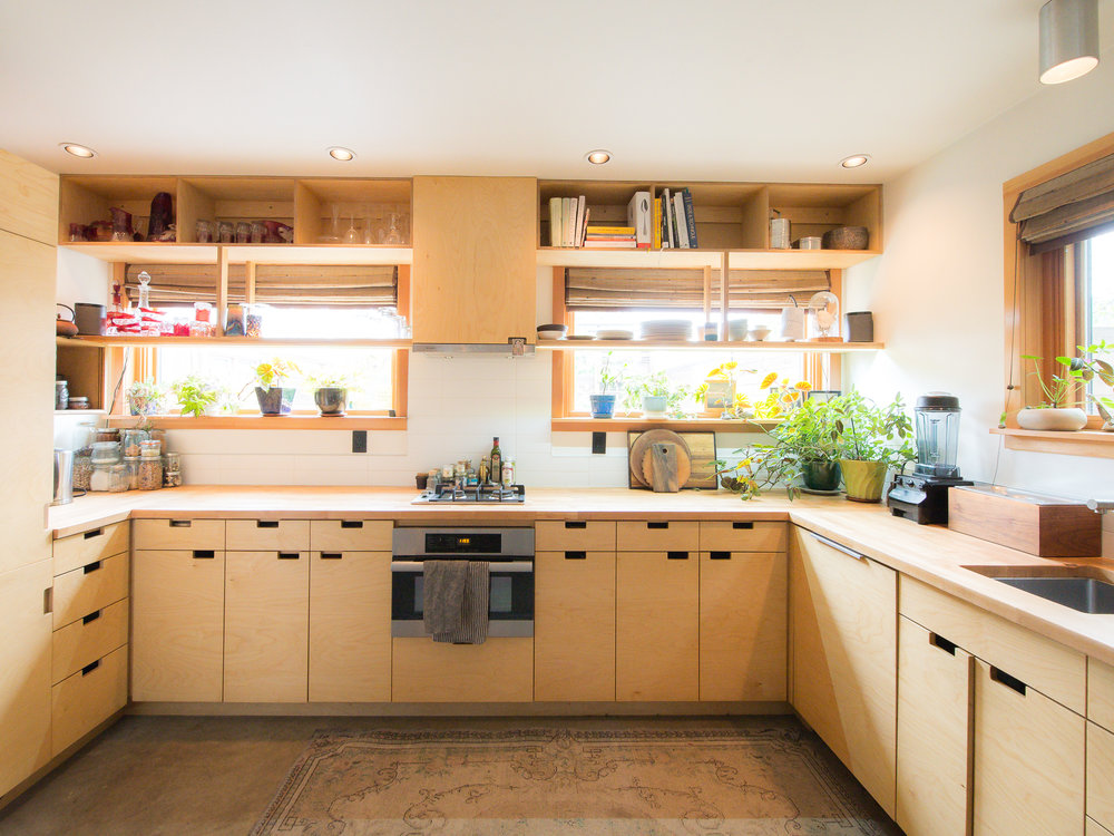 Baltic birch plywood cabinets are paired with wood countertops. The combination speed oven/microwave/convection oven is from Miele.