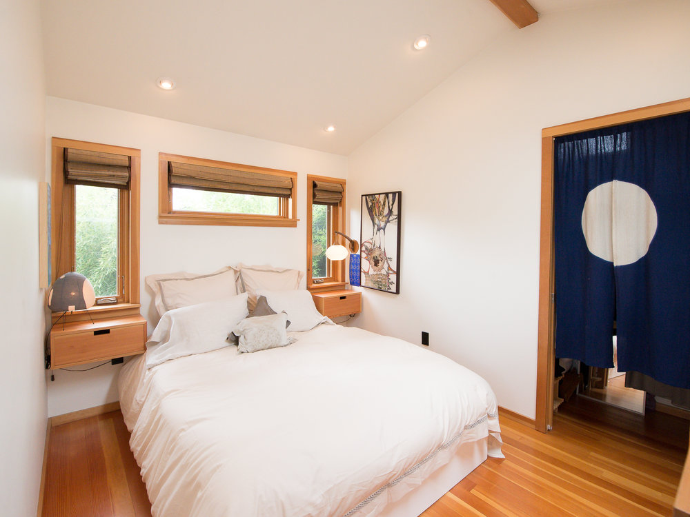 To anchor the bedroom wall, a trio of windows create an altar-like effect with views of the outdoors. A Japanese indigo noren visually opens the space in the doorway, while still accompanied by a pocket door. A grouping of three is visually repeated through the spherical roundness of the paper Noguchi lamp, the mid-century milk glass light and the moon pattern on the noren.