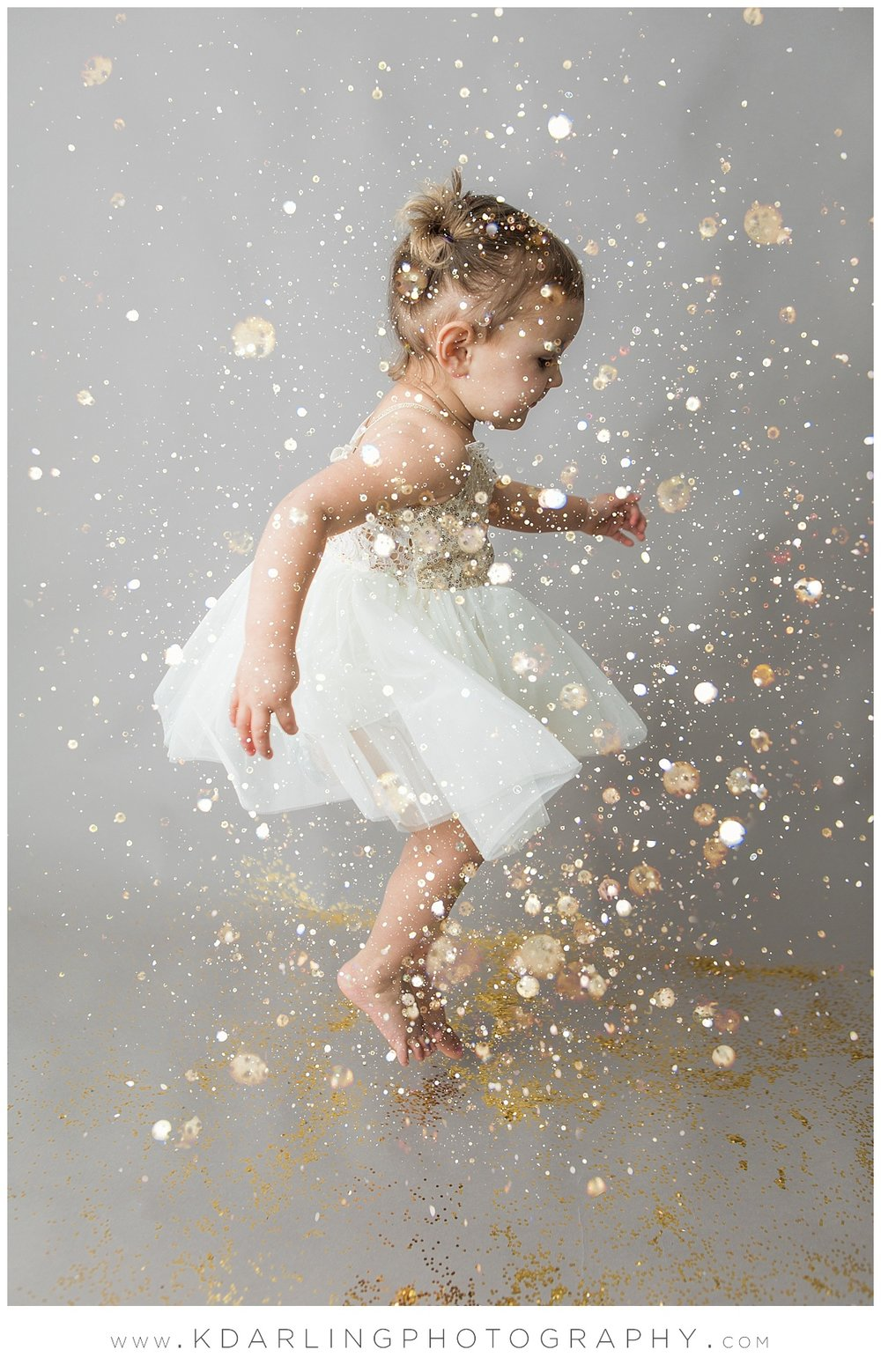Two year old jumping in glitter