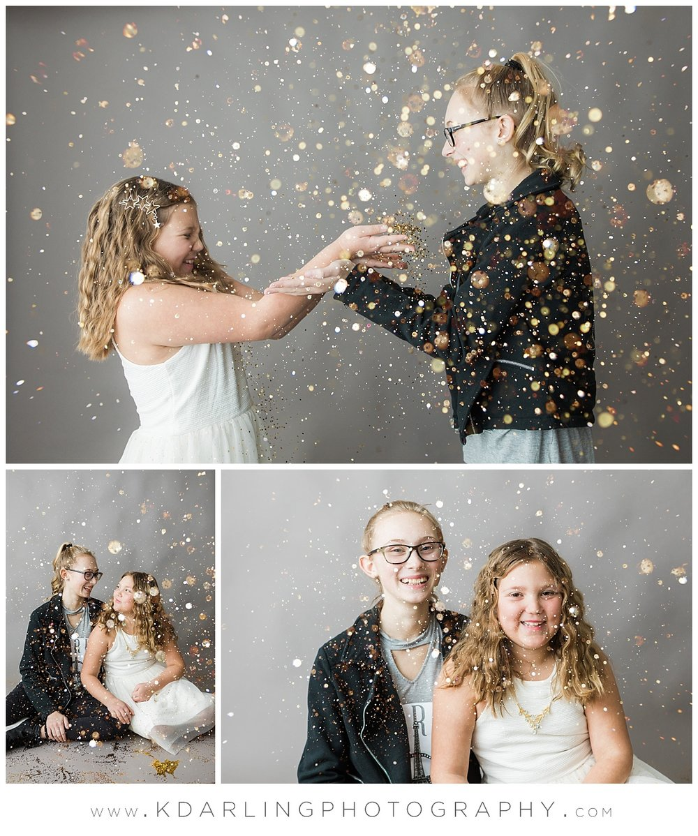 Tween sisters blowing glitter at each other