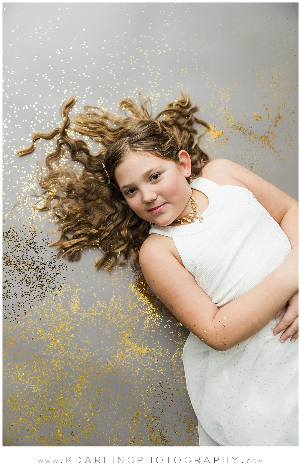 Tween girl in white dress laying in glitter