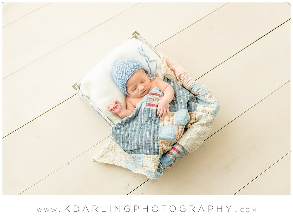 Newborn baby boy on white wood floor