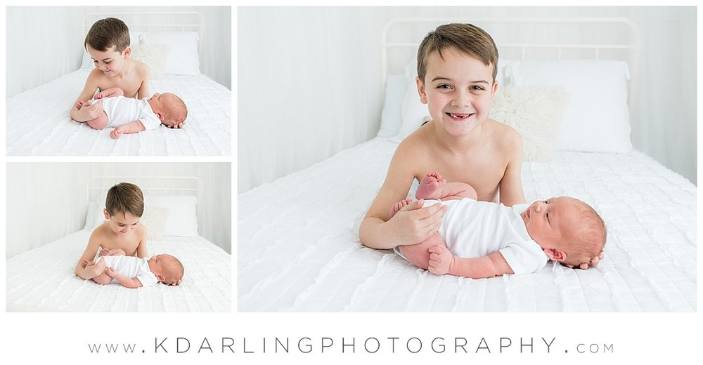 Newborn baby and brother no shirt on white bed