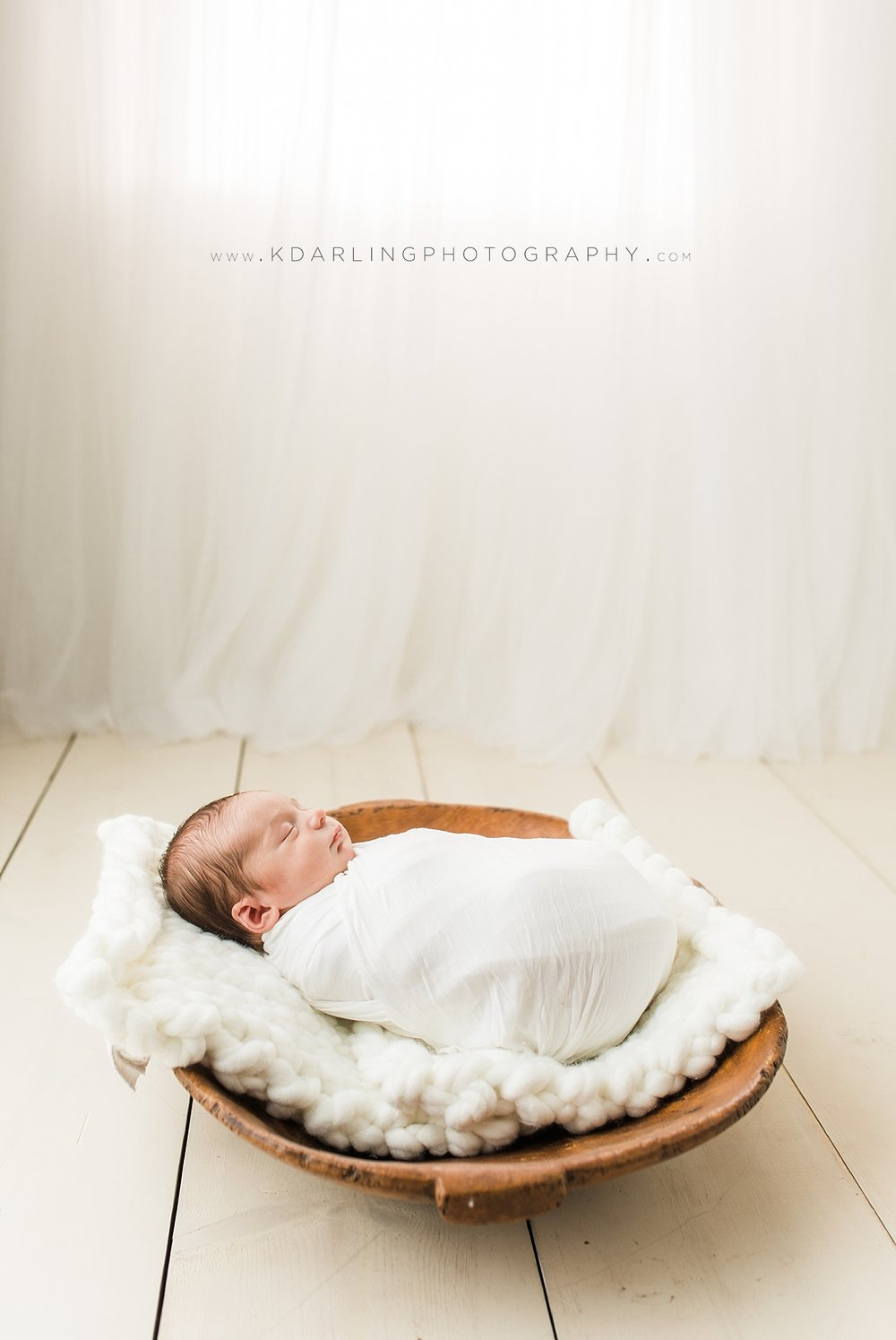 Newborn baby wrapped in white on wood floor