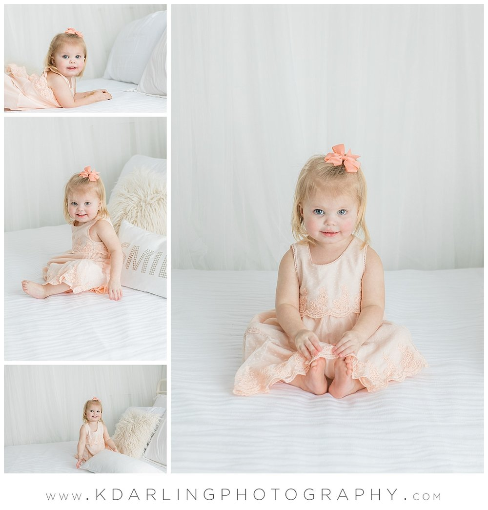 Studio session on white bed with two year old girl