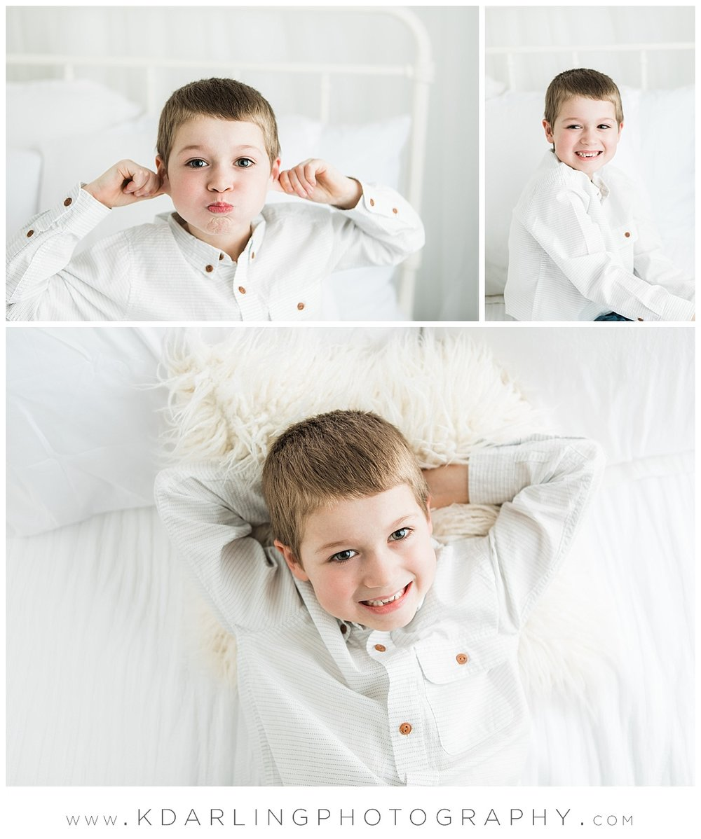 Studio session on white bed smiling six year old boy