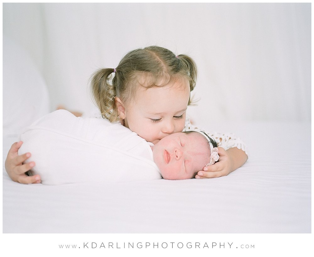 Big sister kisses baby at newborn session.