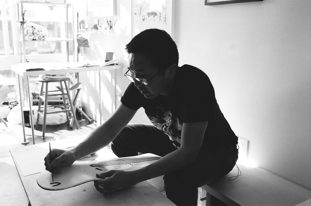 Jeffrey Cheung painting a skate deck.