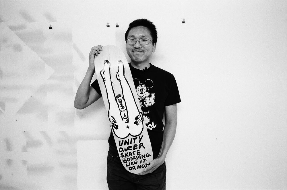 Jeffrey Cheung holding a skate deck he painted.