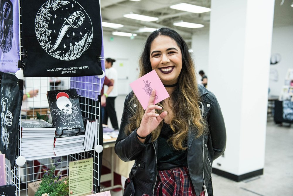 Amrit holds up one of her zines.
