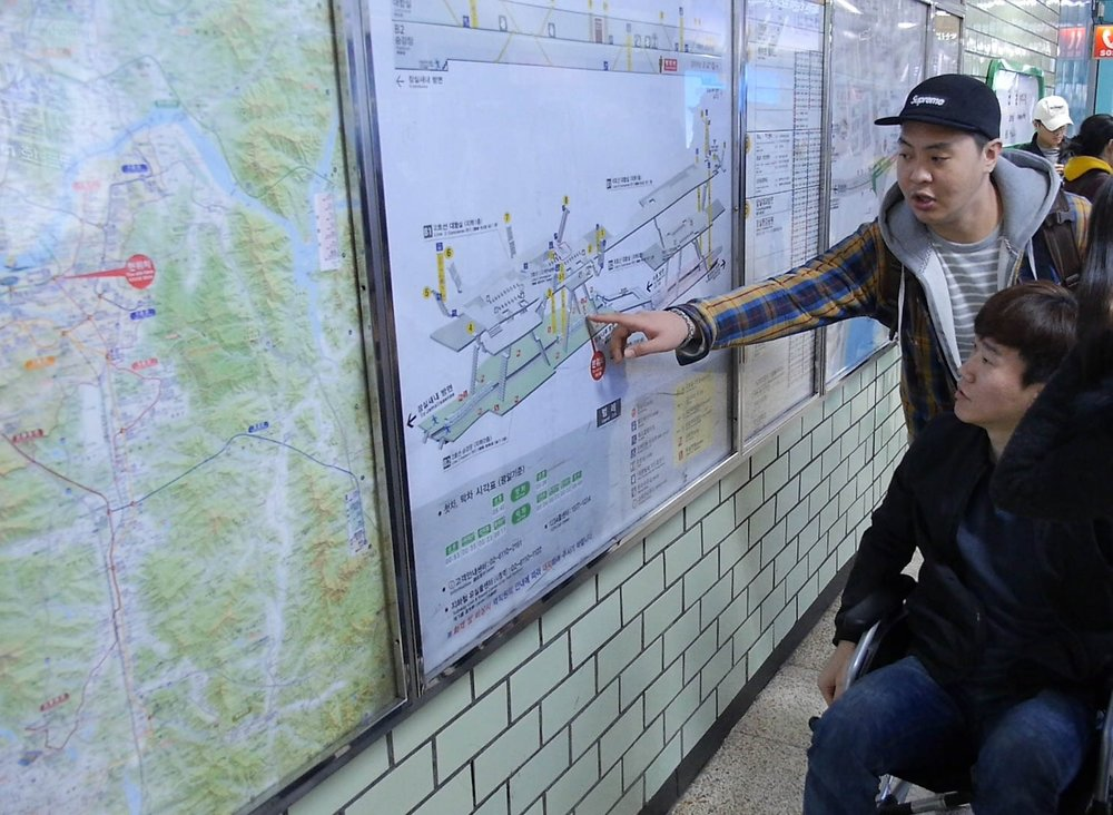 Members from Muui looking at a subway station map in Seoul. Source: Muui.
