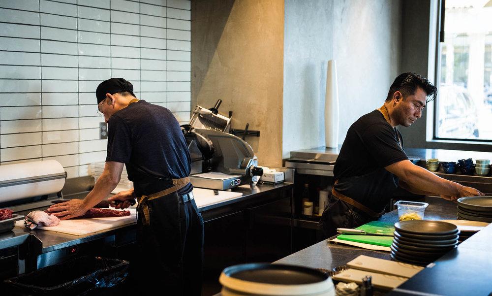 The chefs prepare the delicious meats.