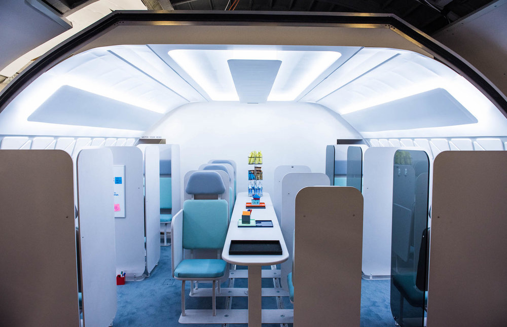 A business center on the plane. These chairs are designed for relaxation and work. There are also private cubicles on the sides for extra privacy.