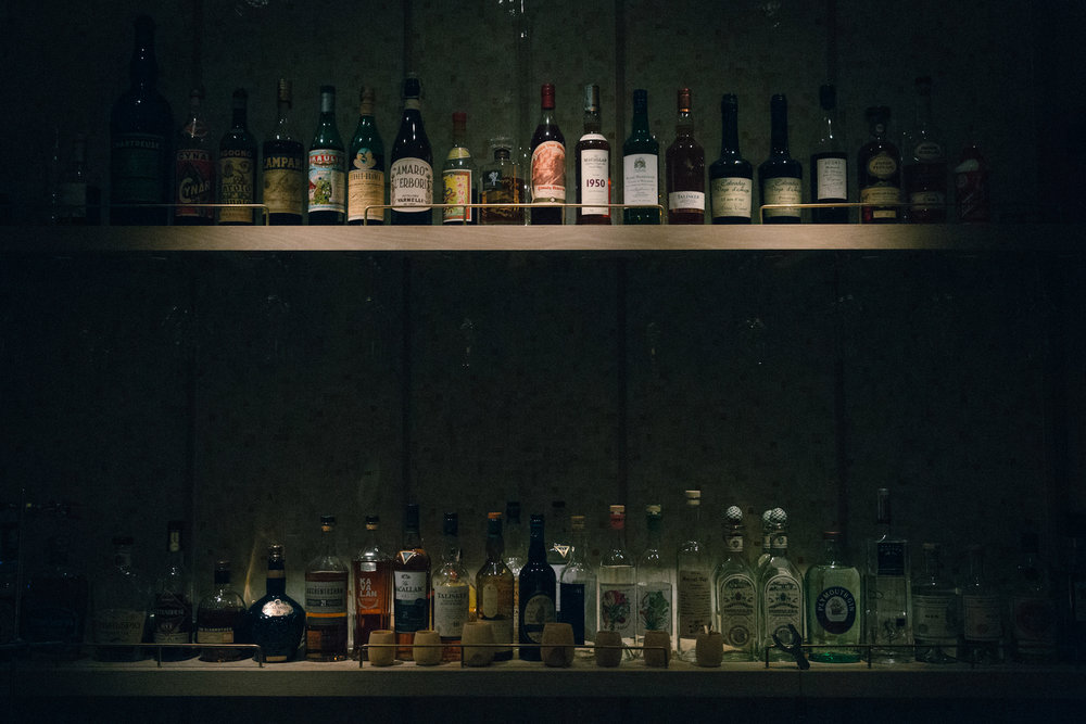 At the bar, a m  oodily lit wall of spirits rests.