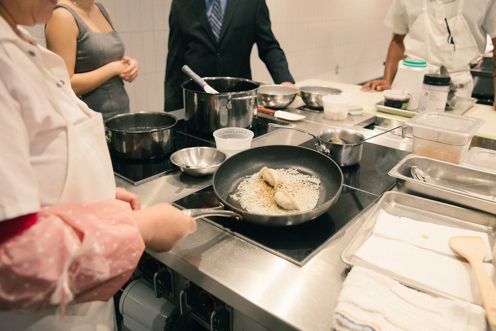 A cook fries the Foie Gras potstickers.