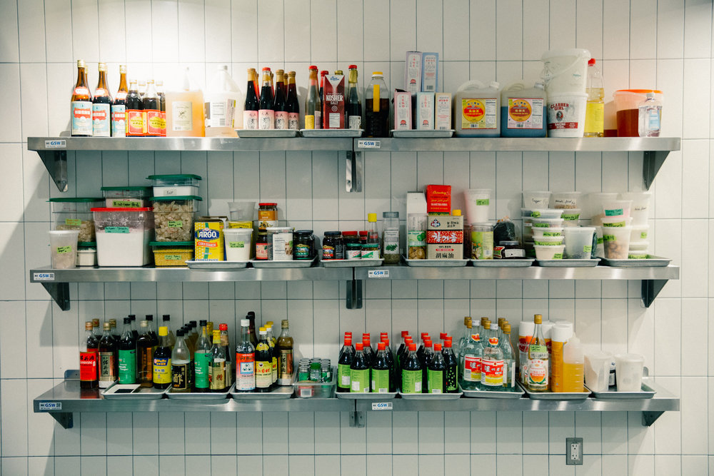 A wall of sauces and spices—some familiar, some specially sourced