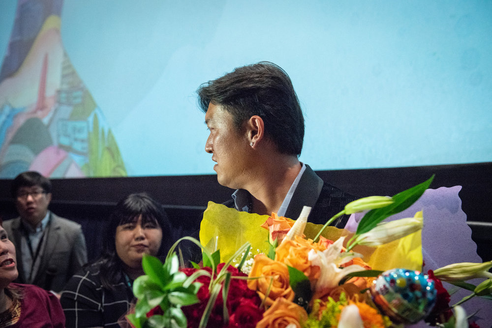Fans give Wang flowers after the premiere.