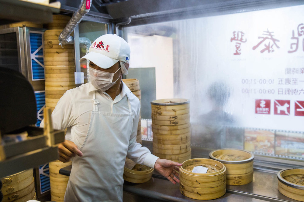 A chef quickly turns to check the orders while switching cooked and uncooked dumplings.