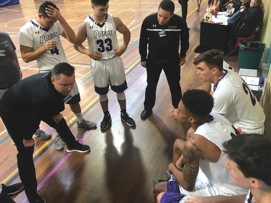 Head Men's Basketball Coach Mark Jensen leans in close during an inspirational sideline speech.