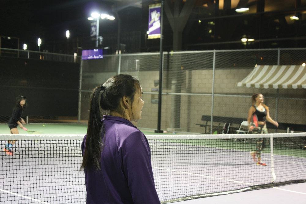 Here,  Whittier College's Head Women' s  Tennis Coach Kristen Yep oberserves her players.