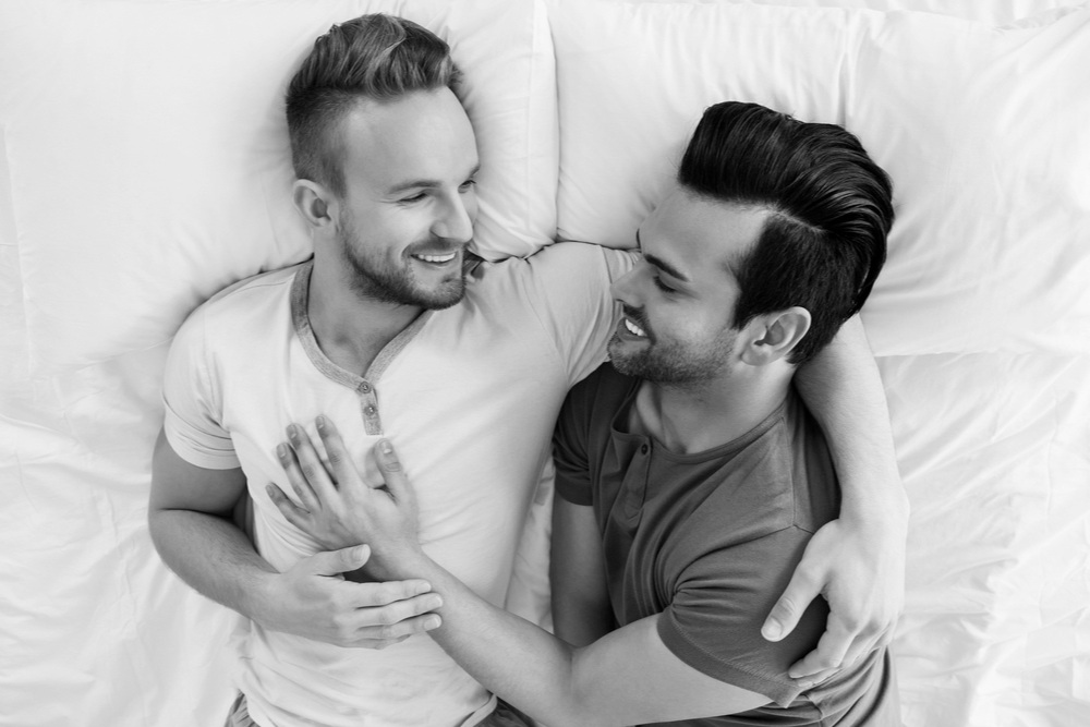 stock-photo-happy-gay-couple-lying-on-bed-at-home-387157258.jpg