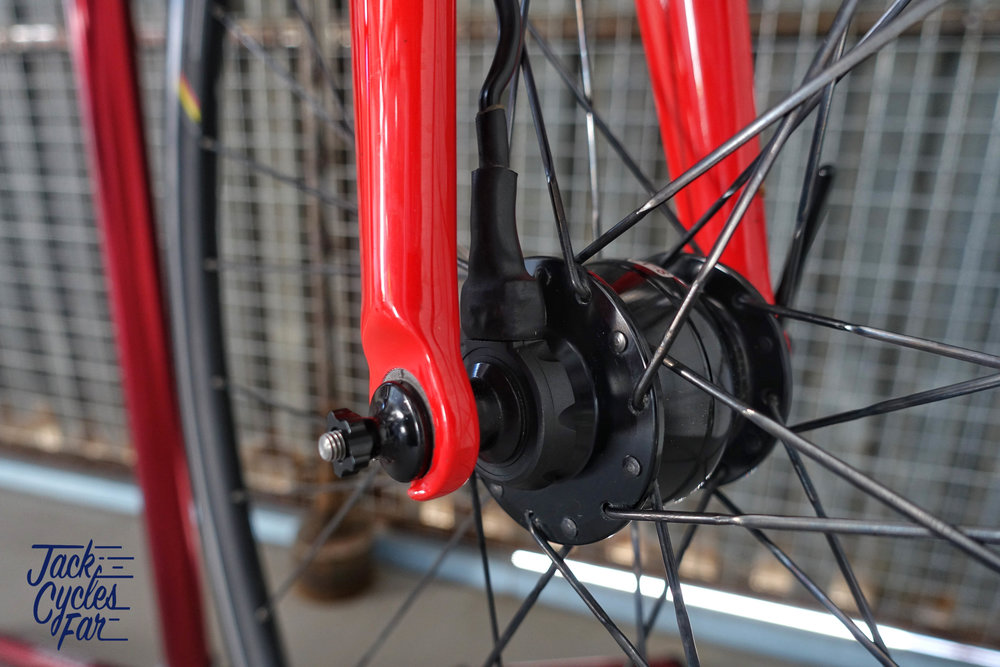 The bar switch connects to the tab on the outer of the dynamo hub and runs up the inside of the fork to the handlebars.  I personally tape the wire to the fork to ensure it does not get tangled in the spokes.