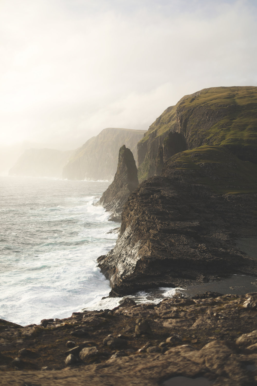 Views of the Bøsdalafossur waterfall falling into the North Atlantic ocean.