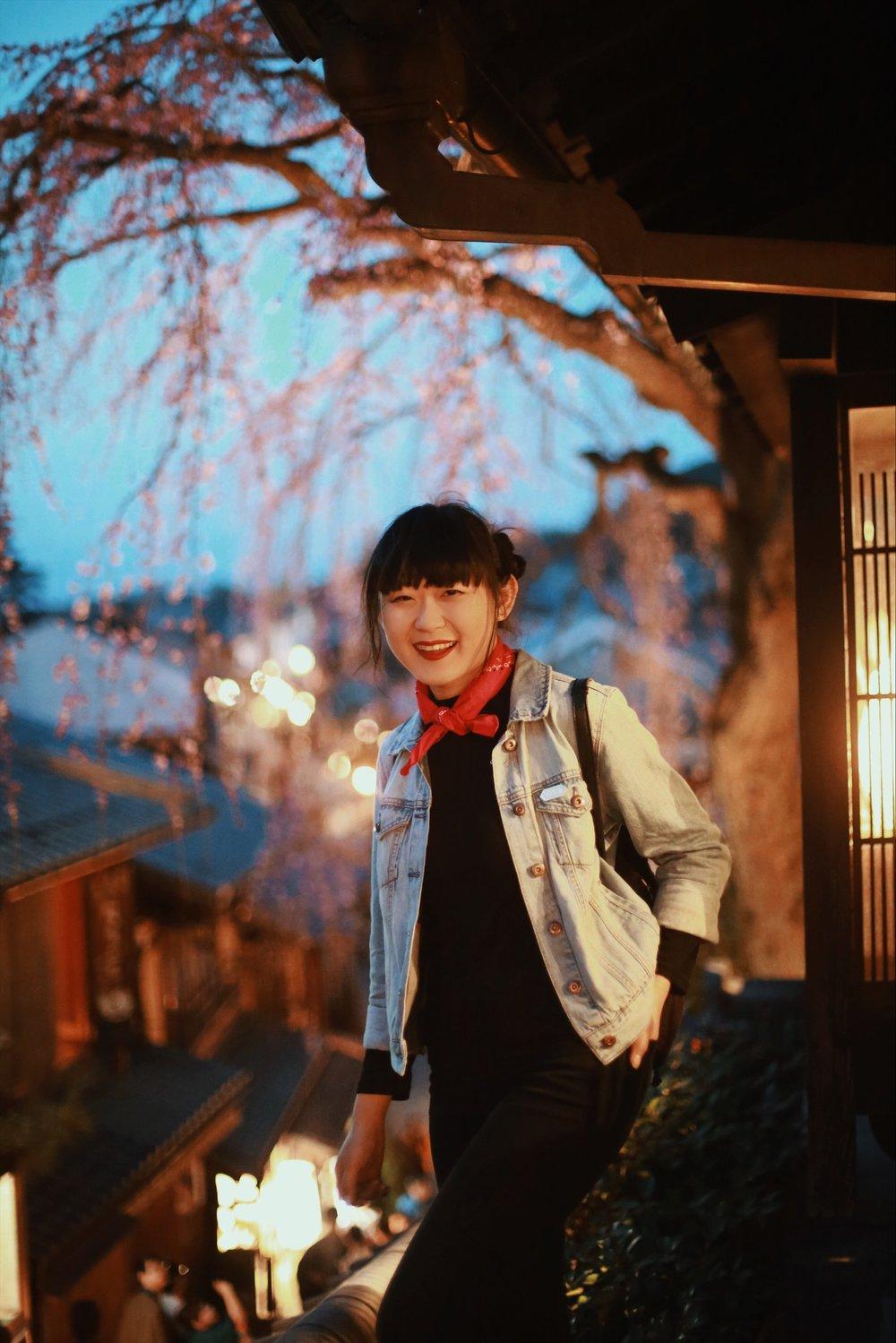 Jen poses by a tree almost in fully cherry blossom splendor overlooking the Ninen-zaka pedestrian street in Higashiyama.