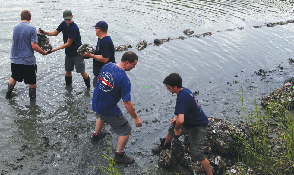 Boy Scout volunteers build a Chuckatuck barrier with bags of oyster shells. by Volvo Penta Photos