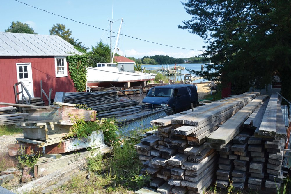 Stacked wood, a red shed, and a deadrise workboat on the railway—this must be the place: Butler's famous Reedville Marine Railway.
