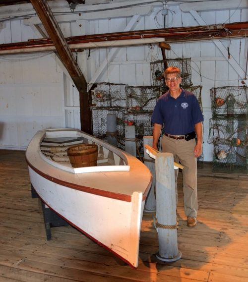 Chesapeake Bay Maritime Museum chief curator Pete Lesher stands beside an original Smith Island crab skiff in the museum's small boat collection. Photo by Dick Cooper.