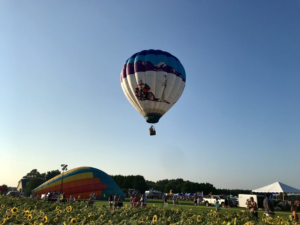 A balloon with designs of motorcycles and cars ascends over the festivalgoers in the late afternoon sun after a lengthy preparation process.