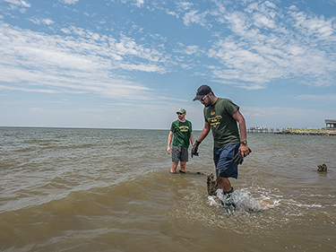 Juan Garzon and Ali Rezaie, doctoral students in coastal engineering at George Mason University, search the shallows for a submerged wave sensor they had planted on the bottom weeks earlier. (Dave Harp)
