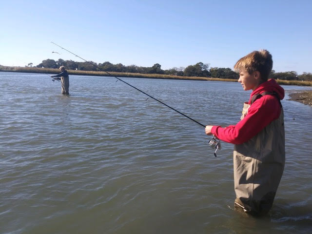Brothers Quin (foreground) and Travis Carroll of Virginia Beach wade the banks of the Lynnhaven River, where they caught dozens of spotted sea trout including a limit for them and their dad, Bob Carroll. (Photo courtesy of Robert Carroll a.k.a Capt. Octopus)